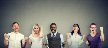 Erfolgreiche Männer und Frauen der jungen Leute feiern einen Sieg stockbild
