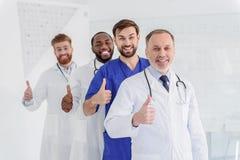 Erfolgreiche männliche Doktoren, die positiv gestikulieren stockbild