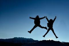Erfolgreiche Paare, die für Freude springen lizenzfreie stockfotografie