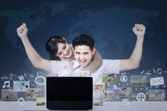 Erfolgreiche Paare mit on-line-Geschäft auf blauer Weltkarte Stockfotos