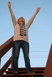 Erfolgreiche reife Frau, die mit den Armen oben erreichen preist Stockfoto