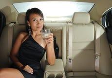 Erfolgreiche schöne asiatische Frau, die in einem Auto sitzt Lizenzfreies Stockfoto