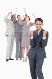 Erfolgreiche Verkäuferin mit zujubelndem Team hinter ihr Stockbild