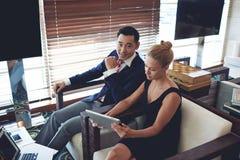 Erfolgreiche weibliche und männliche Unternehmer, die Notenauflage beim zusammenarbeiten verwenden Stockfotografie