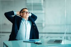 Erfolgreicher älterer Geschäftsmann, der ein Problem oder eine neue Idee erwägend zurück sich entspannen in seinem Stuhl im Büro  lizenzfreies stockbild