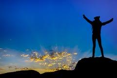 Erfolgreicher Arm der Schattenbildleistungen herauf das Mädchen ist auf Hügel Erfolg mit Sonnenuntergang feiernd stockbild