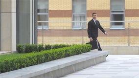 Erfolgreicher attraktiver Geschäftsmann lässt das Gebäude und geht entlang es Langsame Bewegung stock footage