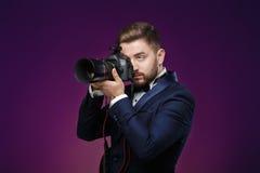 Erfolgreicher Berufsfotograf in der Digitalkamera des Smokingsgebrauches DSLR auf dunklem Hintergrund Lizenzfreies Stockfoto