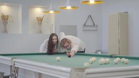 Erfolgreicher blonder bärtiger Mann unterrichtet seine Freundin, Billard zu spielen Überzeugter Mann im weißen Hemd erklärt der F stock video footage