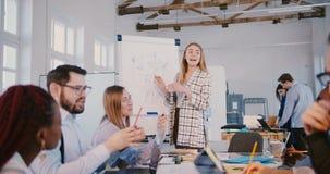 Erfolgreicher blonder Geschäftsfraumentor, der Finanzdiagramm Team von multiethnischen Kollegen auf Seminar erklärt stock footage