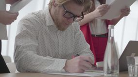 Erfolgreicher blonder Mann des Portr?ts in den Gl?sern, die in einem hellen bequemen B?ro mit netbook am Tabellenunterzeichnen si stock video footage