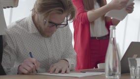 Erfolgreicher blonder Mann des Portr?ts in den Gl?sern, die in einem hellen bequemen B?ro mit netbook am Tabellenunterzeichnen si stock video