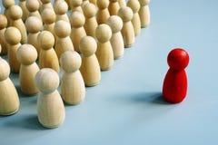 Erfolgreicher Führer des Teams als rote Figürchen aus der Menge heraus stockfotografie