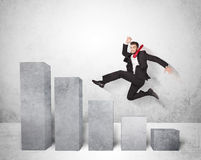 Erfolgreicher Geschäftsmann, der über Diagramme auf Hintergrund springt Stockbilder