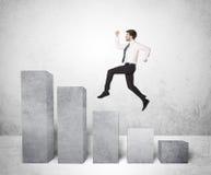 Erfolgreicher Geschäftsmann, der über Diagramme auf Hintergrund springt Stockfotos