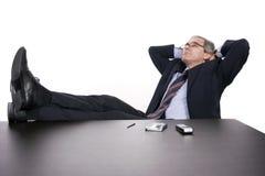 Erfolgreicher Geschäftsmann, der über seinem Schreibtisch sich entspannt lizenzfreie stockfotos