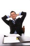 Erfolgreicher Geschäftsmann, der über seinem Schreibtisch sich entspannt Lizenzfreies Stockfoto