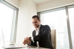 Erfolgreicher Geschäftsmann, der auf Armbanduhr schaut Stockbild