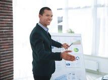 Erfolgreicher Geschäftsmann, der auf eine Flip-Chart mit den Finanzinformationen zeigt stockfotografie