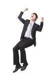 Erfolgreicher Geschäftsmann, der auf etwas sitzt Lizenzfreie Stockfotos