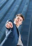 Erfolgreicher Geschäftsmann, der auf Kamera über Bürogebäudehintergrund zeigt Lizenzfreies Stockfoto
