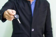 Erfolgreicher Geschäftsmann, der einen Autoschlüssel anbietet Stockfotografie