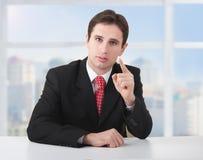 Erfolgreicher Geschäftsmann, der ernsthaft am Schreibtisch sitzt Lizenzfreies Stockfoto