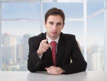 Erfolgreicher Geschäftsmann, der ernsthaft am Schreibtisch sitzt Stockfotografie
