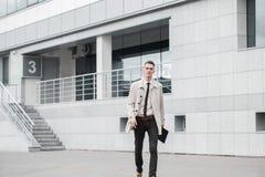 Erfolgreicher Geschäftsmann, der hinunter die Straße geht und am Tag lächelt Stockbilder