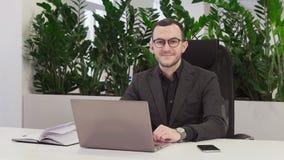Erfolgreicher Geschäftsmann in der Klage lächelnd am Arbeitsplatz stock video footage