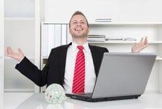 Erfolgreicher Geschäftsmann, der mit den Händen oben und Laptop lacht Stockfotografie