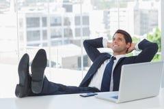 Erfolgreicher Geschäftsmann, der mit seinen Füßen auf seinem Schreibtisch sich entspannt Lizenzfreie Stockfotos