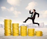 Erfolgreicher Geschäftsmann, der oben auf Goldmünzgeld springt Stockbild
