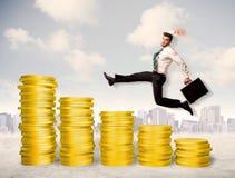Erfolgreicher Geschäftsmann, der oben auf Goldmünzgeld springt Stockfotografie