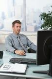 Erfolgreicher Geschäftsmann, der am Schreibtisch arbeitet Lizenzfreies Stockbild