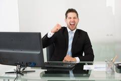 Erfolgreicher Geschäftsmann, der am Schreibtisch schreit Stockfotos