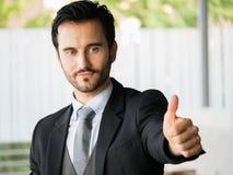 Erfolgreicher Geschäftsmann, der sich Daumen, Büroangestellter, unternehmerische Entscheidungen zeigt Stockbilder