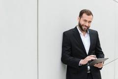 Erfolgreicher Geschäftsmann, der unter Verwendung einer Tablette steht Stockbild