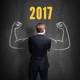 Erfolgreicher Geschäftsmann, der vor einer Tafel mit 2017 steht Stockfoto