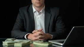 Erfolgreicher Geschäftsmann, der vor Laptop, Geld erscheint auf Tabelle sitzt stock video