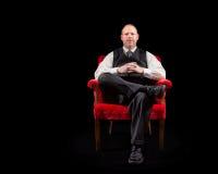 Erfolgreicher Geschäftsmann in der Weste und Bindung, die im roten Samtstuhl auf schwarzem Hintergrund sitzt Lizenzfreies Stockbild