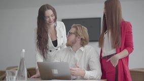 Erfolgreicher Geschäftsmann des Porträts in den Gläsern, die in einem hellen bequemen Büro mit netbook am Tisch sitzen Zwei Mädch stock footage