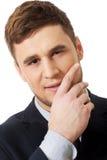 Erfolgreicher Geschäftsmann mit dem Finger unter Kinn Stockfoto