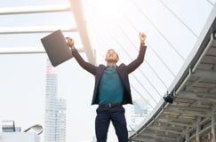 Erfolgreicher Geschäftsmann mit den Armen up und den ledernen Briekäse halten Stockbilder