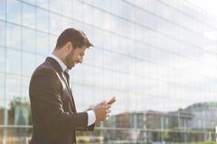Erfolgreicher Geschäftsmann oder Arbeitskraft, die in der Klage mit Mobiltelefon stehen stockfoto