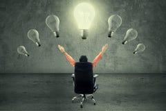 Erfolgreicher Geschäftsmann unter Glühlampe Stockfotos