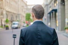 Erfolgreicher Geschäftsmann von der Rückseite in der Klage, die sicher in der Stadt steht stockfoto
