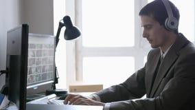 Erfolgreicher Gesch?ftsmann in den Kopfh?rern, die an seinem Schreibtisch, arbeitend auf einem Computer durch das panoramische Fe stock footage