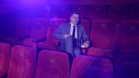 Erfolgreicher Gesch?ftsmann in einer Klage, die allein in einem Kino sitzt Portr?t stock video footage