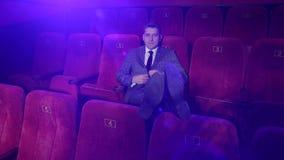 Erfolgreicher Gesch?ftsmann in einer Klage, die allein in einem Kino sitzt Portr?t stock footage